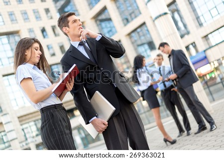Young businessman and his secretary standing in front of office building.  Businessman carrying in one hand a closed laptop and thinking, and the secretary keeps the planner. - stock photo