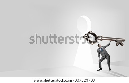Young businessman and lifting big key above head