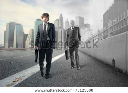 Young businessman and older businessman walking on a street - stock photo