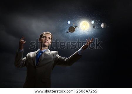 Young businessman and planets of space spinning around