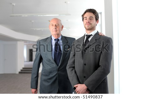 Young businessman and satisfied senior businessman - stock photo