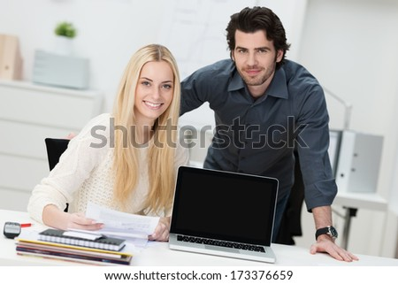 Young businessman and woman in the office sitting at a desk with their laptop screen turned to face the camera with copyspace for your text or advertisement - stock photo