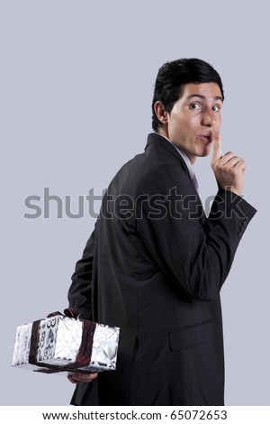 young businessman asking for silence because he have a gift surprise to offer (isolated on gray) - stock photo