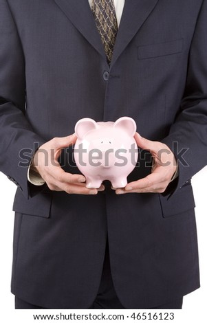 Young businessman at table with a piggy bank - stock photo