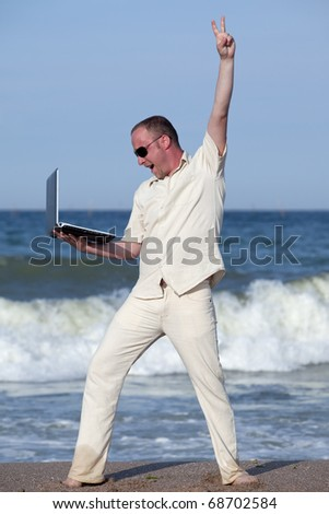 Young businessman at the beach with his laptop happy about success