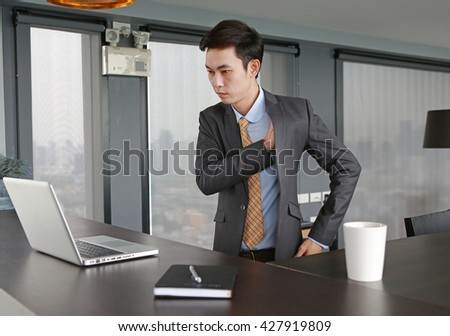 Young businessman at the table and wearing suit - stock photo