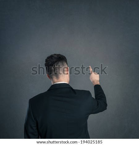 Young businessman back view with pointing finger and copy space isolated on dark background. Studio shot.