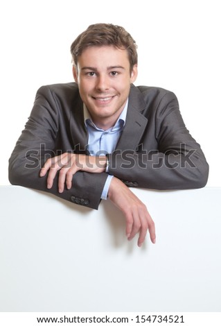 Young businessman behind a signboard - stock photo