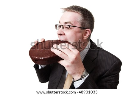 young businessman bites chocolate pie - stock photo
