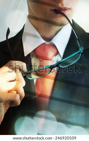 Young businessman bitting the glasses hand - stock photo