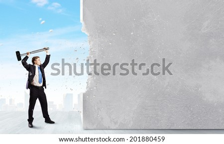 Young businessman breaking cement wall with hammer