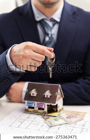 Young businessman broker offering house for rent holding keyring. Closeup of male real estate agent sitting in the office with building model on desk.  - stock photo
