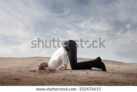 Young businessman burying his head in the sand - stock photo