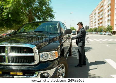 Young businessman by modern car