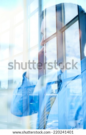 Young businessman calling in office window - stock photo