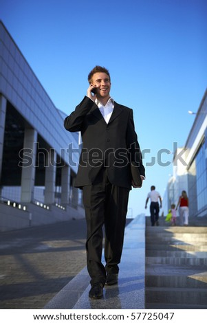 Young businessman calling on mobile phone, outdoor. - stock photo