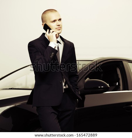 Young businessman calling on the phone at the car - stock photo