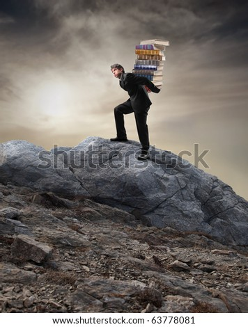 Young businessman carrying a stack of books while climbing a mountain - stock photo