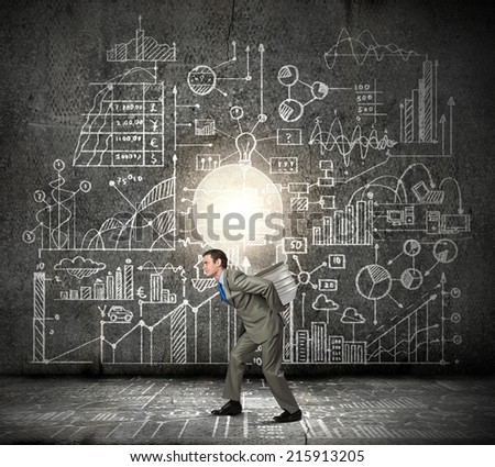 Young businessman carrying big light bulb on back - stock photo
