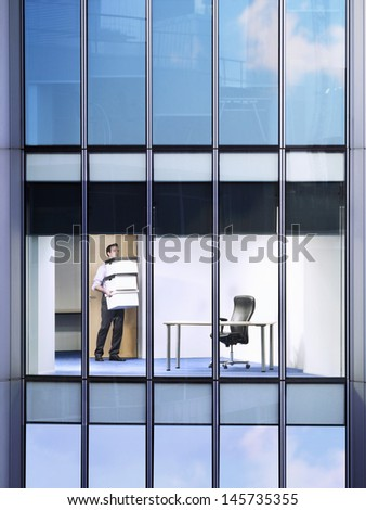 Young businessman carrying stack of boxes in office - stock photo
