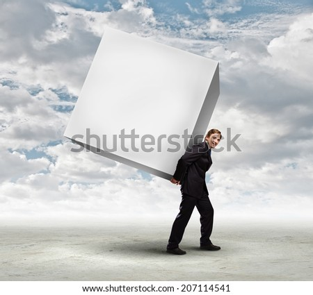 Young businessman carrying white blank cube. Place for text - stock photo