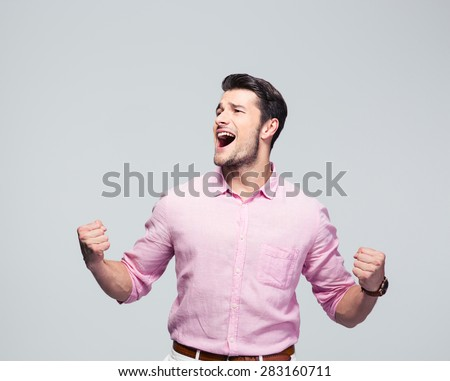 Young businessman celebrating his success over gray background - stock photo
