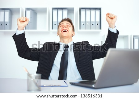 Young businessman celebrating his success with arms raised at his workplace in bright office - stock photo