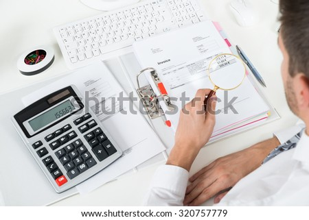 Young Businessman Checking Invoice With Magnifying Glass At Desk - stock photo