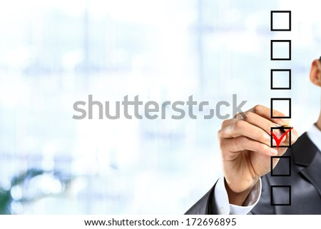 Young businessman checking mark on checklist with marker. - stock photo
