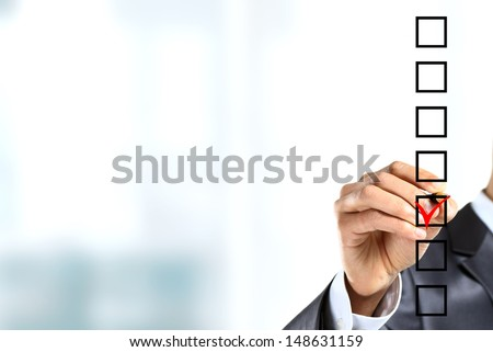 Young businessman checking mark on checklist with marker. Isolated on white. - stock photo