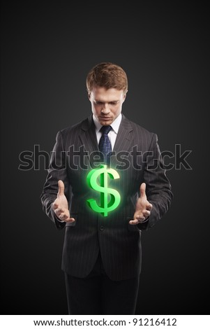 Young  businessman chooses a green US dollar sign. On a black background - stock photo