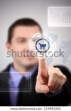 Young businessman choosing shopping cart symbol - stock photo