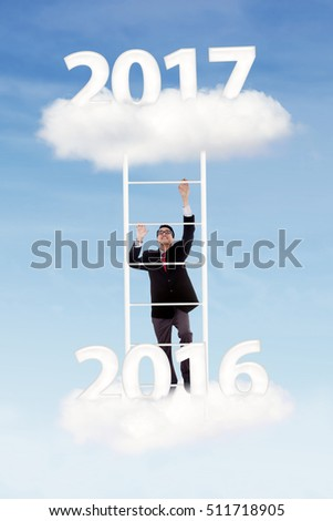 Young businessman climbing upward with ladder from cloud number 2016 to number 2017 in the blue sky
