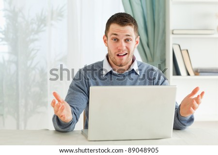 Young businessman clueless about his notebook in his home office - stock photo