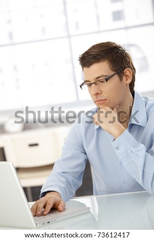 Young businessman concentrating on computer work, looking at laptop screen, thinking.? - stock photo