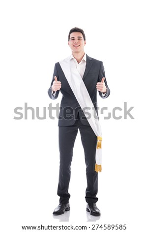 Young businessman confidently posing wearing winning ribbon or sash, showing thumbs up isolated in white background - stock photo