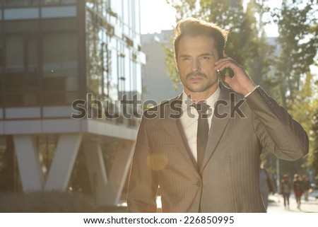 Young businessman conversing on cell phone outdoors - stock photo