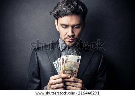 Young businessman counting money - stock photo
