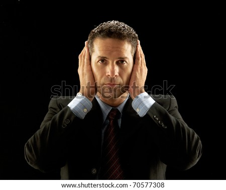 Young businessman covering his ears on black background. - stock photo