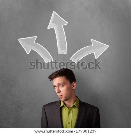 Young businessman deciding with sketched arrows above his head - stock photo