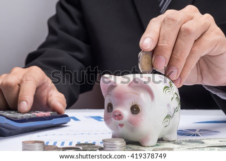 Young businessman depositing money in piggy bank.