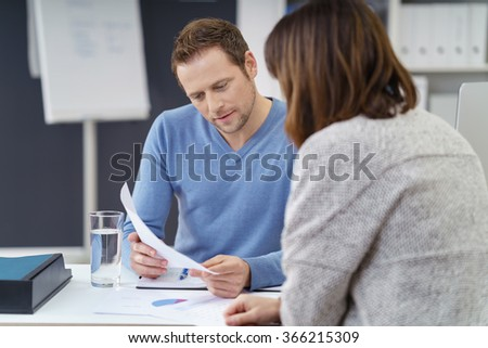 Young businessman discussing a document with a female co-worker as they share a table at the office