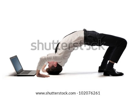 Young businessman doing acrobatics in front of a laptop - stock photo