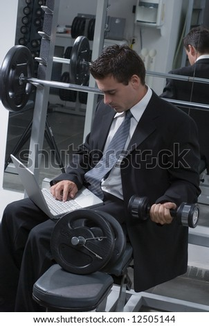 Young businessman doing biceps curls while working on his laptop - stock photo