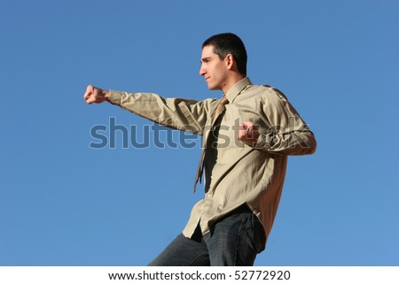 Young businessman doing exercises outdoors