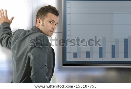 Young businessman doing presentation at meetingroom standing front of big LCD display, presenting charts. - stock photo