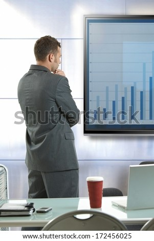 Young businessman doing presentation explaining diagram at meetingroom front of LCD display. - stock photo