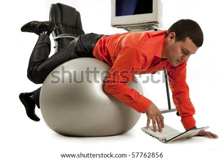 Young businessman doing push-ups and looking on laptop screen. - stock photo