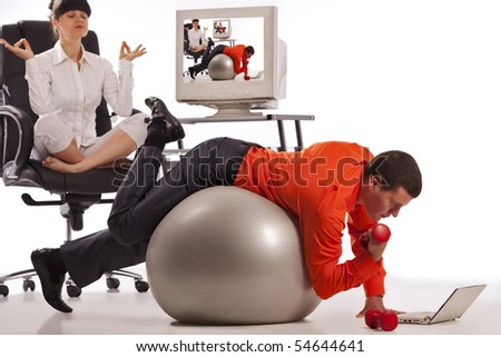 Young businessman doing push-ups with dumbbells, looking on laptop screen. His colleague, doing yoga on the office chair - stock photo