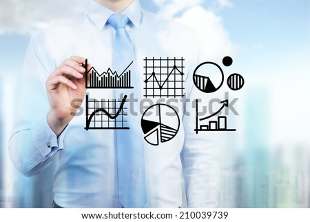 Young businessman drawing a set of the graphs including pie chart, line graph and sketches in a glass screen. - stock photo